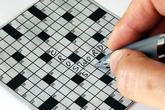 Solving the cross word puzzle. From the newspaper Royalty Free Stock Images