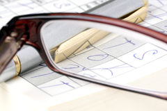 Solving crosswords. Crosswords on which are placed glasses and pencil Stock Photos