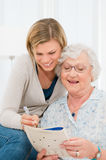 Solving crosswords puzzle together. Active senior lady solving crosswords puzzle with the help of her young granddaughter royalty free stock photos