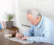 Solving crosswords. Senior man in pajamas with reading glasses sitting at table and solving crosswords royalty free stock photo