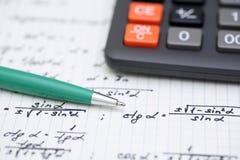 Solving Mathematical Problem. Equations close-up. Homework. Solving Mathematical Problem. Focus on pen. Shallow depth of field Stock Photos