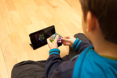 Solving Megaminx. Lviv, Ukraine - March 31, 2013: Little boy solving Megaminx, sitting on floor and  watching video with tablet. The Megaminx is a dodecahedron Stock Photos