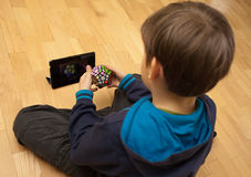 Solving Megaminx. Lviv, Ukraine - March 31, 2013: Little boy solving Megaminx, sitting on floor and  watching video with tablet. The Megaminx is a dodecahedron Royalty Free Stock Photography