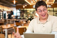 Solving a problem. Man with a laptop in a restaurant has a good idea Stock Images