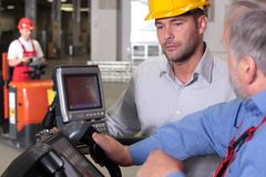 Solving problems in warehouse. Supervisor talking to forklift operator in warehouse royalty free stock photo