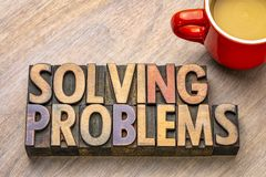 Solving problems text in wood type. Solving problems word abstract in vintage letterpress wood type printing blocks with a cup of coffee stock photos