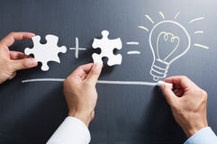 Solving puzzle together. Drawing light bulb on blackboard. Royalty Free Stock Photography