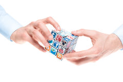 Solving Rubick's Cube with social media logos. A hands holding rubik's cube with logotypes of well-known social media brand's stock photo