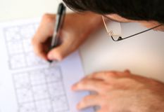 Solving sudoku. Man holding a pen and trying too solve sudoku Royalty Free Stock Photo