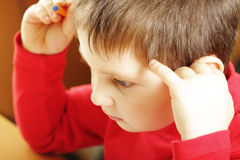 Solving task. Little boy in red shirt thinking of solving task selective focus royalty free stock photography