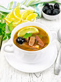 Solyanka with black olives in white bowl on board. Soup saltwort with lemon, meat, pickles, tomato sauce and olives in a white bowl, towel, parsley on a wooden Royalty Free Stock Image