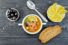 Solyanka in bowl on black board top. Soup saltwort with lemon, meat, pickles, tomato sauce olives in a bowl, bread and a spoon on the background of a wooden Stock Photos