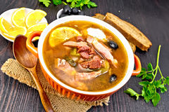 Solyanka in bowl on board. Soup saltwort with lemon, meat, pickles, tomato sauce and olives in a bowl on a sacking, bread on a background of a dark wooden board stock image