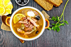 Solyanka in bowl on board top. Soup saltwort with lemon, meat, pickles, tomato sauce olives in a bowl on a sacking, bread on a background of a wooden board from Royalty Free Stock Images