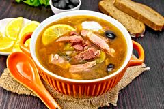 Solyanka in bowl on sackcloth. Soup saltwort with lemon, meat, pickles, tomato sauce olives in a bowl on a sacking, bread on a wooden board background Royalty Free Stock Image