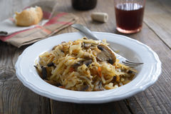Solyanka. Braised cabbage with mushrooms and carrot on a rustic table Stock Photos