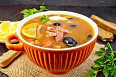 Solyanka with lemon and black olives in bowl on dark board. Soup saltwort with lemon, meat, pickles, tomato sauce olives in a bowl on a sacking, bread and stock photo