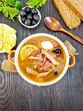 Solyanka with lemon in bowl on board top. Soup saltwort with lemon, meat, pickles, tomato sauce olives in a bowl on a sacking, bread, parsley and spoon on a Stock Images