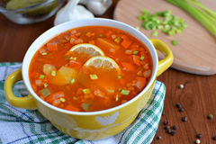 Solyanka mix soup with sausages, potatoes and lemon. Delicious  Solyanka mix soup with sausages, potatoes and lemon Stock Photo