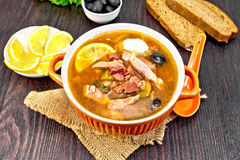 Solyanka with olives in bowl on sackcloth. Soup saltwort with lemon, meat, pickles, tomato sauce olives in a bowl on a sacking, bread, parsley and spoon on a Royalty Free Stock Image