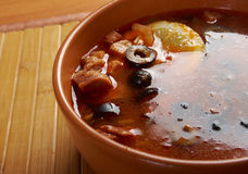 Solyanka on the plate. Solyanka, Russian soup with beef,sausage,chicken and lemon, olives Stock Images