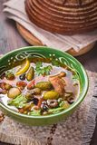 Solyanka soup bowl. Traditional Russian spicy and sour soup solyanka closeup in a bowl on table Royalty Free Stock Photo