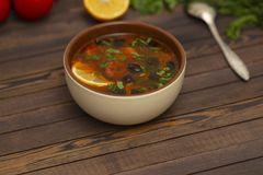 Solyanka soup with lemon, meat, pickles, tomato sauce and olives Traditional Russian dish solyanka. Solyanka soup with lemon, meat, pickles, tomato sauce and royalty free stock images