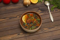 Solyanka soup with lemon, meat, pickles, tomato sauce and olives Traditional Russian dish solyanka. Solyanka soup with lemon, meat, pickles, tomato sauce and royalty free stock photography