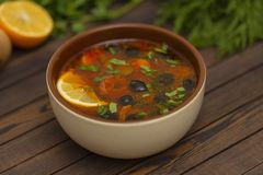 Solyanka soup with lemon, meat, pickles, tomato sauce and olives Traditional Russian dish solyanka. Solyanka soup with lemon, meat, pickles, tomato sauce and stock photography