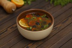 Solyanka soup with lemon, meat, pickles, tomato sauce and olives Traditional Russian dish solyanka. Solyanka soup with lemon, meat, pickles, tomato sauce and royalty free stock image