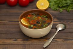 Solyanka soup with lemon, meat, pickles, tomato sauce and olives Traditional Russian dish solyanka. Solyanka soup with lemon, meat, pickles, tomato sauce and stock image