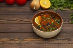 Solyanka soup with lemon, meat, pickles, tomato sauce and olives Traditional Russian dish solyanka. Solyanka soup with lemon, meat, pickles, tomato sauce and stock photo
