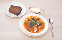 Solyanka - thick soup with different types of meat, with sour cr. Solyanka - thick soup with different types of meat - served with lemon, bread and sour cream Stock Image