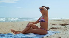 solzaschitnyh玻璃的一名美丽的妇女基于海的岸并且看  影视素材