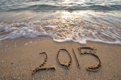 2015 som är handskriven på sandstranden royaltyfri foto