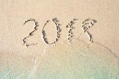2018 som är skriftlig i havssanden royaltyfri bild