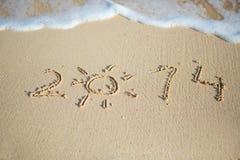 2014 som är skriftlig i sand royaltyfri fotografi