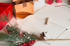 2017 som är skriftlig på anteckningsboken med garneringar för nya år Arkivbilder