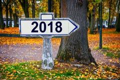 2018 som är skriftlig på en gammal fransk roadsign, höstlig bakgrund Arkivfoton