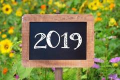 2019 som är skriftlig på ett trätecken, solrosor och lösa blommor arkivfoto