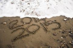 2015 som är skriftlig på sand arkivfoto