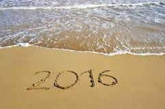 2016 som är skriftlig på sandstranden - begrepp för lyckligt nytt år Royaltyfria Bilder