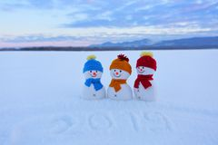 2019 som är skriftlig på snön Le snögubben med hattar och halsdukar står på fältet med snö Liggande med berg royaltyfri fotografi
