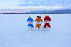 2019 som är skriftlig på snön Le snögubben med hattar och halsdukar står på fältet med snö Liggande med berg royaltyfri foto