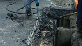 som bakgrund är kan den använda stenlägga vägen Arbetare som lägger stenmastixasfalt under gatan som reparerar arbeten arkivfilmer
