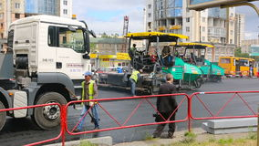 som bakgrund är kan den använda stenlägga vägen Arbetare som lägger stenmastixasfalt under gatan som reparerar arbeten lager videofilmer