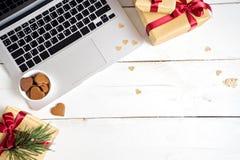 som bakgrund är kan det använda julillustrationtemat Dator, gåvor och kakor på den wood tabellen royaltyfri fotografi