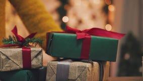 som bakgrund är kan det använda julillustrationtemat Den unga kvinnan sätter gåvorna under julgranen I defocusingen lager videofilmer
