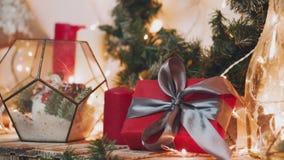 som bakgrund är kan det använda julillustrationtemat Den unga kvinnan sätter gåvorna under julgranen I defocusingen arkivfilmer