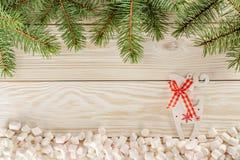som bakgrund är kan det använda julillustrationtemat din text för korthälsningsställe Vita träbakgrund och marshmallower i ställe Royaltyfri Foto